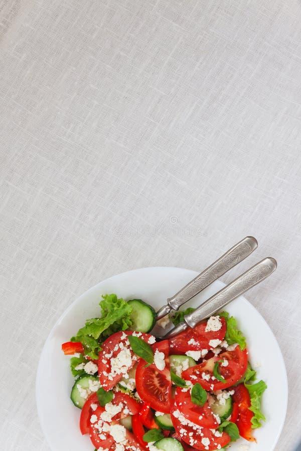 Σαλάτα Shopska σε ένα άσπρο πιάτο σε ένα άσπρο τραπεζομάντιλο Το concep στοκ φωτογραφίες