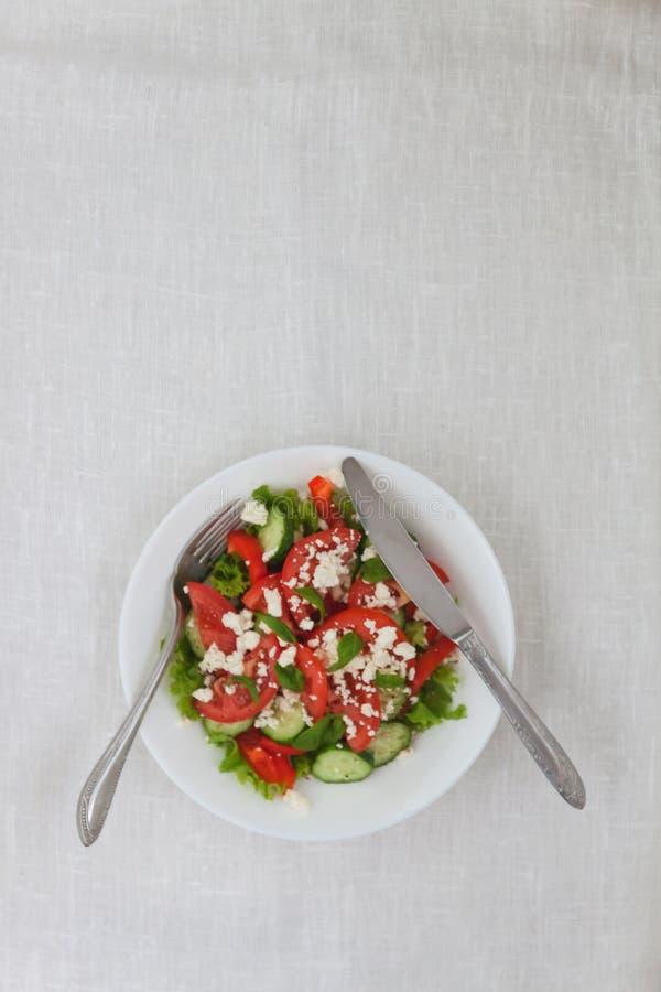 Σαλάτα Shopska σε ένα άσπρο πιάτο σε ένα άσπρο τραπεζομάντιλο Το concep στοκ εικόνες με δικαίωμα ελεύθερης χρήσης
