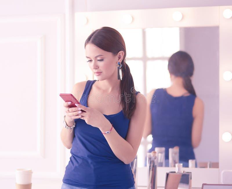 Σαλόνι ομορφιάς γυναικών χρησιμοποιώντας και εξετάζοντας το κινητό τηλέφωνο στοκ εικόνα με δικαίωμα ελεύθερης χρήσης