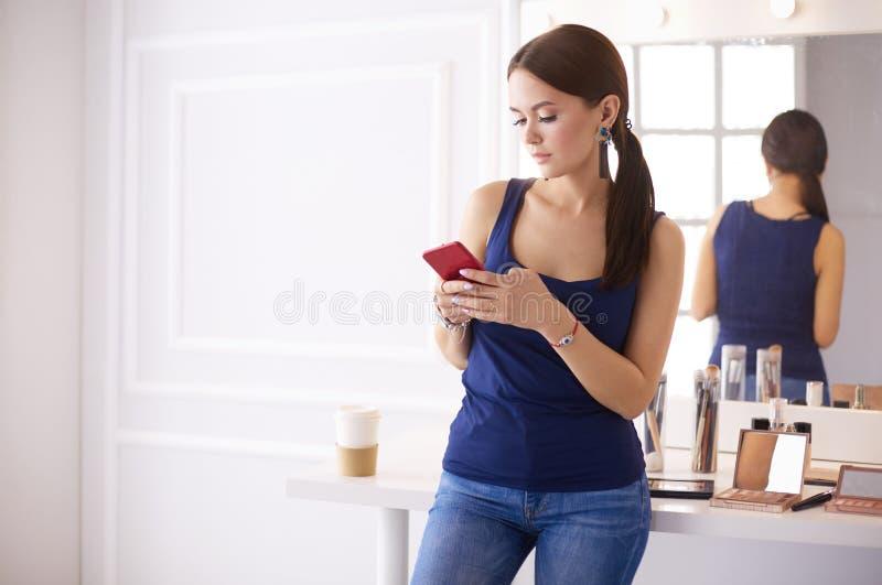 Σαλόνι ομορφιάς γυναικών χρησιμοποιώντας και εξετάζοντας το κινητό τηλέφωνο στοκ εικόνα