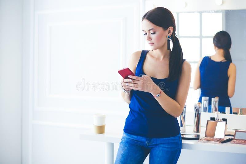 Σαλόνι ομορφιάς γυναικών χρησιμοποιώντας και εξετάζοντας το κινητό τηλέφωνο στοκ εικόνες