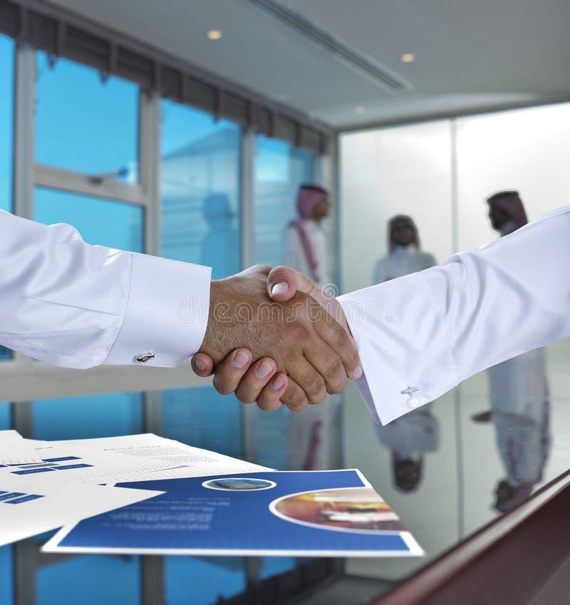 Σαουδάραβας - αραβικοί επιχειρηματίες που τινάζουν τα χέρια, και που κάνουν τη συμφωνία ή το α στοκ εικόνες