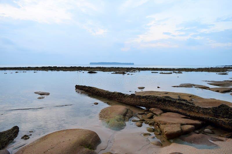 Σαφές διαφανές νερό στην ακτή με το μπλε ουρανό πρωινού με τις αφηρημένες μορφές στο χώμα στοκ φωτογραφία