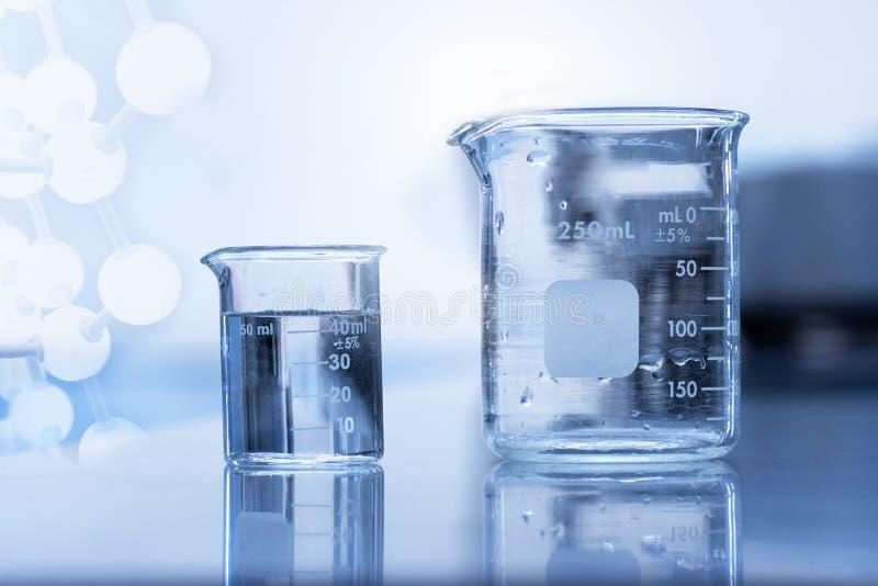 Σαφής κούπα δύο με το νερό στο χημικό υπόβαθρο εργαστηριακής έρευνας επιστήμης στοκ φωτογραφία με δικαίωμα ελεύθερης χρήσης