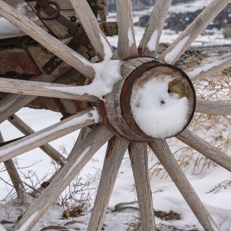 Σαφής τετραγωνικός στενός επάνω της ξύλινης ρόδας ενός παλαιού βαγονιού εμπορευμάτων ενάντια σε μια χιονώδη έκταση το χειμώνα στοκ εικόνες με δικαίωμα ελεύθερης χρήσης