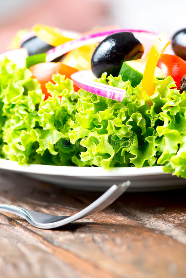 Σαλάτα με τα λαχανικά και πράσινα στο πιάτο στον ξύλινο πίνακα στενό στοκ εικόνες