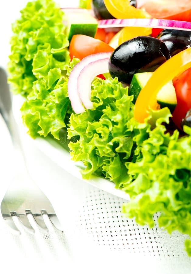 Σαλάτα με τα λαχανικά και πράσινα στο πιάτο στο επιτραπέζιο ύφασμα με τα FO στοκ φωτογραφία με δικαίωμα ελεύθερης χρήσης