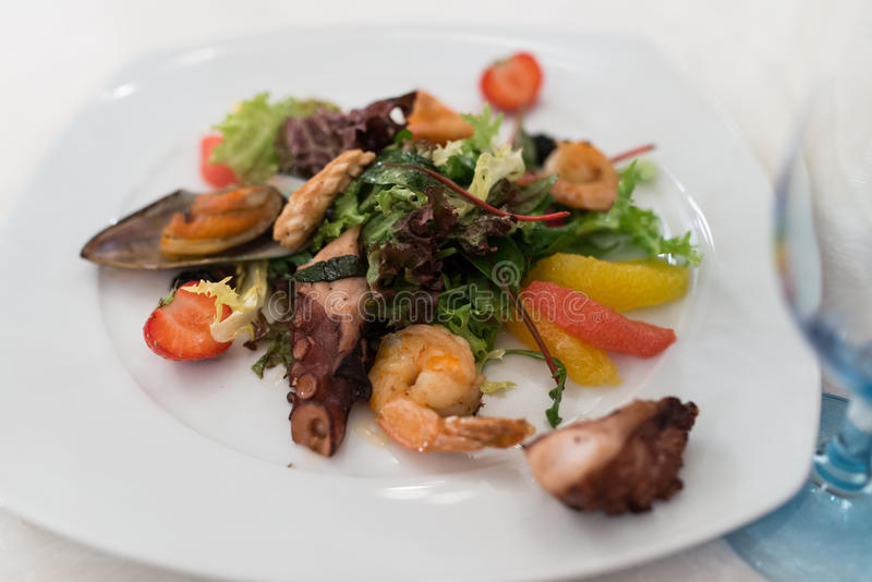 Σαλάτα με τα θαλασσινά, το χταπόδι, τη φράουλα, τα εσπεριδοειδή και τα πράσινα στοκ εικόνες