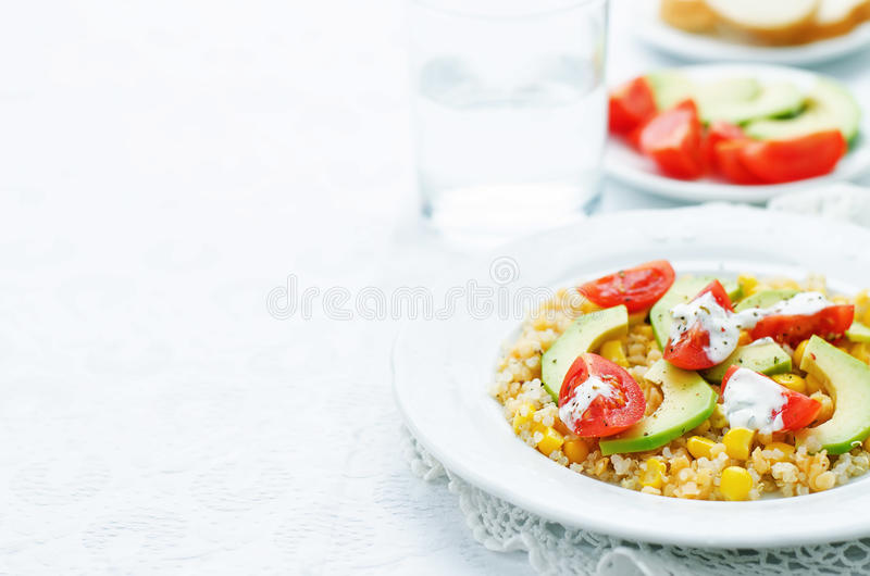 Σαλάτα με quinoa, τις κόκκινες φακές, το καλαμπόκι, το αβοκάντο και την ντομάτα με το yo στοκ φωτογραφία