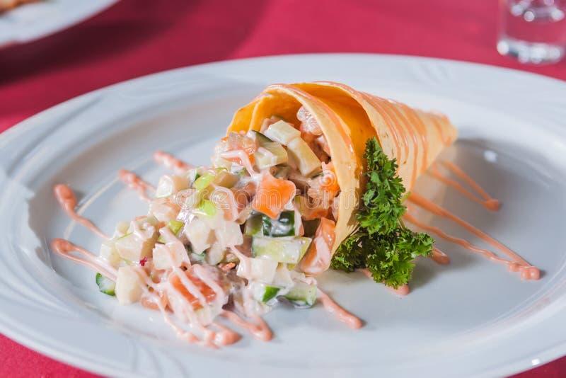 Σαλάτα σε μια σάλτσα και τα πράσινα κώνων βαφλών στοκ εικόνα