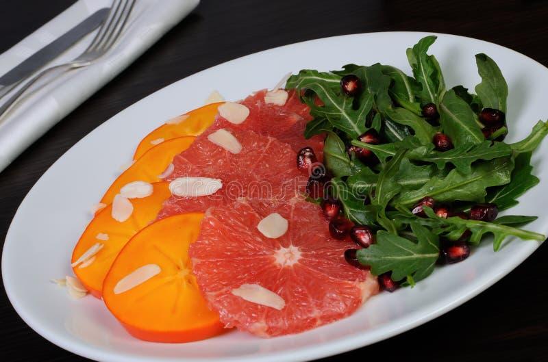 Σαλάτα της σαλάτας γκρέιπφρουτ, persimmon, ροδιών και πυραύλων στοκ εικόνες