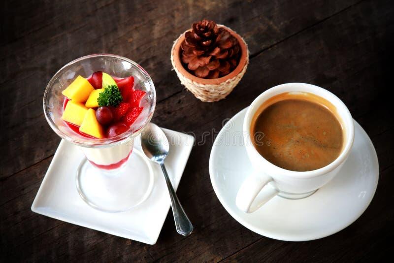 Σαλάτα φρούτων με την πουτίγκα ζελατίνας στο γυαλί και τον καφέ στο άσπρο φλυτζάνι στοκ εικόνα