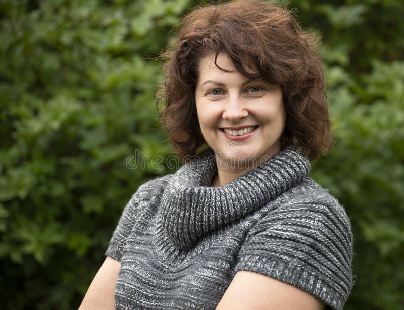 Σγουρή γυναίκα στο γκρίζο πουλόβερ στη φύση στοκ φωτογραφία με δικαίωμα ελεύθερης χρήσης