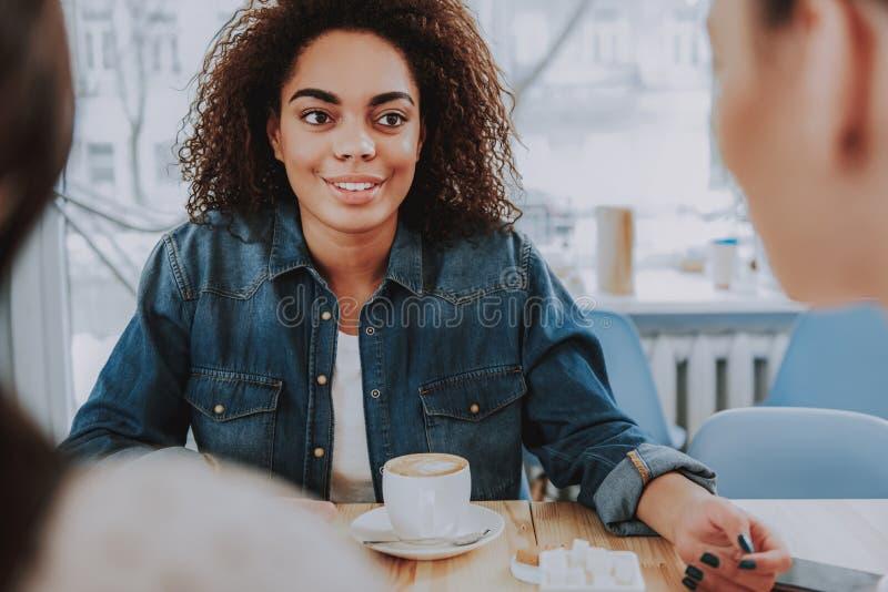 Σγουρή γυναίκα της Νίκαιας που μιλά στους φίλους της στον καφέ στοκ εικόνες με δικαίωμα ελεύθερης χρήσης