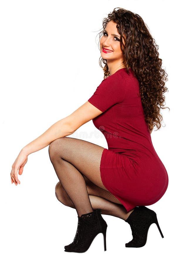 Σγουρή ελκυστική ευτυχής γυναίκα στο κόκκινο φόρεμα και τα υψηλά τακούνια στοκ εικόνα