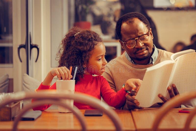 Σγουρή κόρη που ακούει το βιβλίο ανάγνωσης πατέρων της προσεκτικά στοκ φωτογραφίες