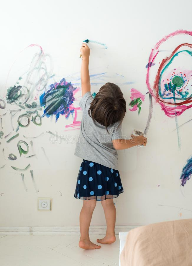 Σγουρός χαριτωμένος λίγο κορίτσι μικρών παιδιών που χρωματίζει με το χρώμα χρωμάτων και τον τοίχο βουρτσών Εργασίες του παιδιού στοκ φωτογραφίες