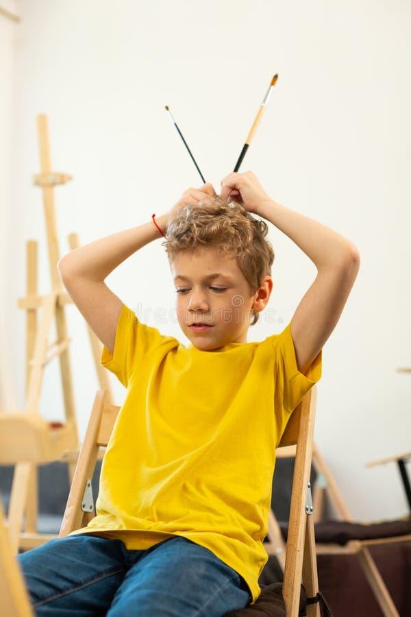Σγουρό αγόρι που κρατά δύο βούρτσες ζωγραφικής που κάθονται το σχολείο τέχνης ν στοκ φωτογραφίες