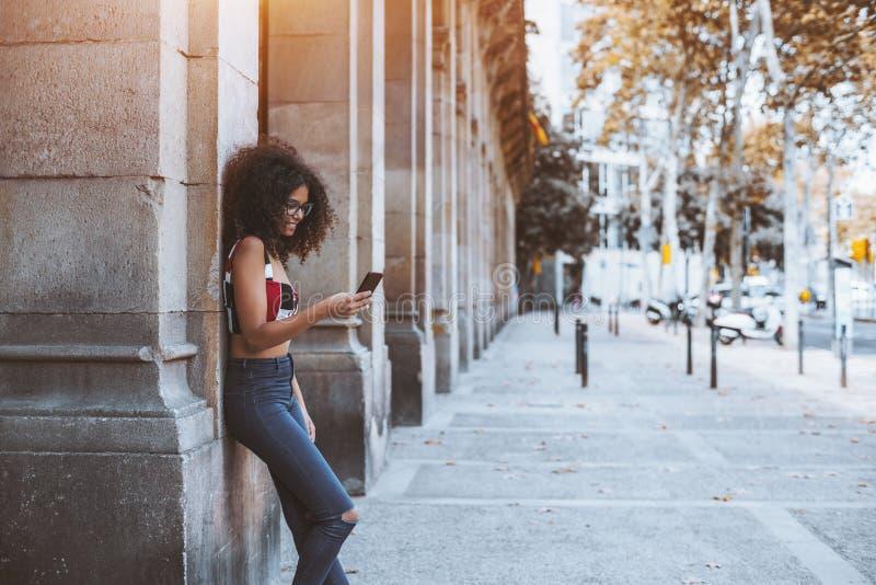 Σγουρό κορίτσι με το κινητό τηλέφωνο που κλίνει ενάντια σε μια υπαίθρια στήλη στοκ εικόνες με δικαίωμα ελεύθερης χρήσης