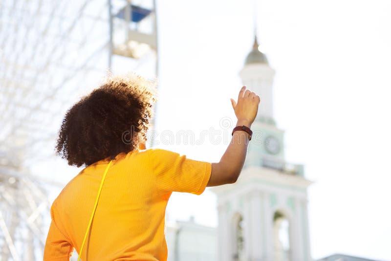 Σγουρό κορίτσι στην κίτρινη μπλούζα που απαιτεί στο φίλο στοκ εικόνα