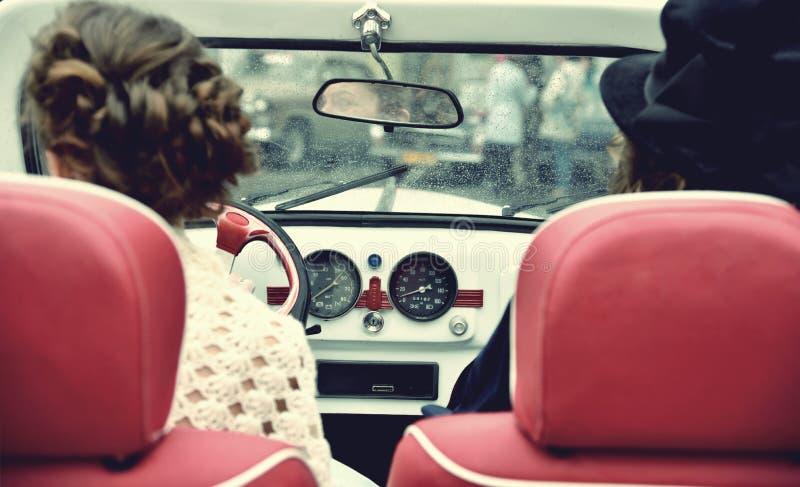 Σγουρό κορίτσι δύο στο μεσαιωνικό φόρεμα στα εκλεκτής ποιότητας αυτοκίνητα κόκκινος τρύγος ύφους κρίνων απεικόνισης στοκ φωτογραφίες με δικαίωμα ελεύθερης χρήσης