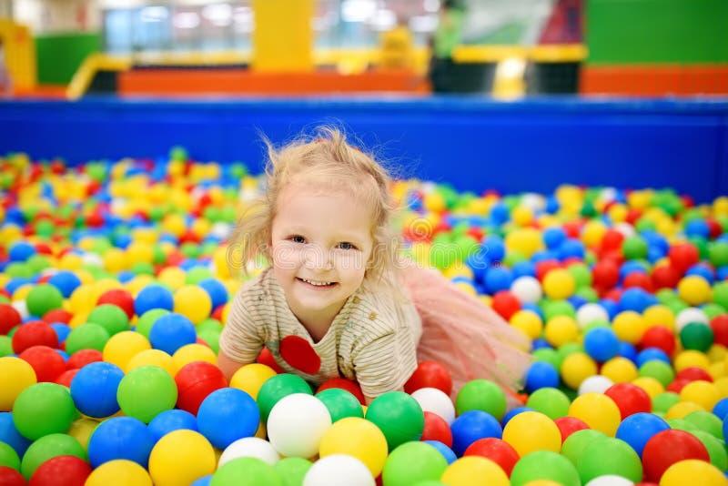 Σγουρό μικρό κορίτσι που έχει τη διασκέδαση στο κοίλωμα σφαιρών με τις ζωηρόχρωμες σφαίρες στοκ εικόνες με δικαίωμα ελεύθερης χρήσης