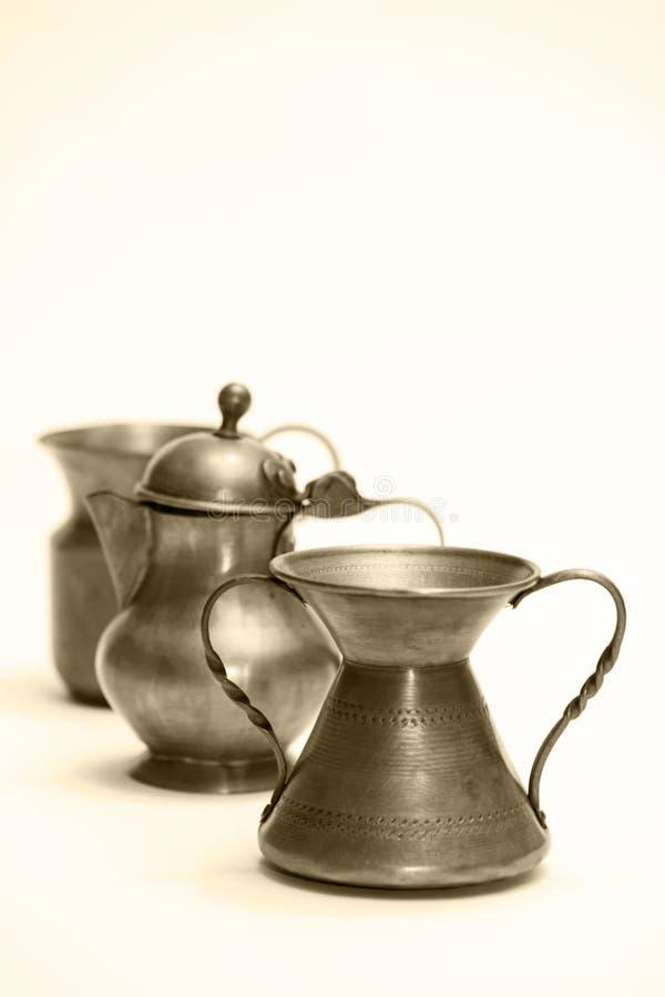 Σειρά από μικρά διακοσμητικά χάλκινα αντικείμενα απομονωμένα σε λευκό φόντο, σε ασπρόμαυρο - φωτογραφία στοκ εικόνα