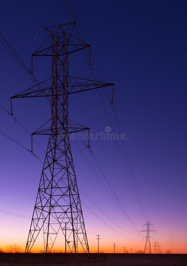 Σειρά πύργων ηλεκτροφόρων καλωδίων στην μπλε ώρα στοκ φωτογραφία