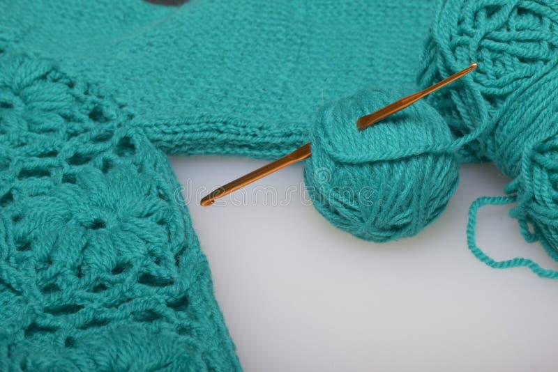 Σειρές του νήματος για το σμαραγδένιο χρώμα πλεξίματος και των γάντζων για το πλέξιμο Σε ένα έτοιμο πλεκτό προϊόν στοκ φωτογραφία με δικαίωμα ελεύθερης χρήσης