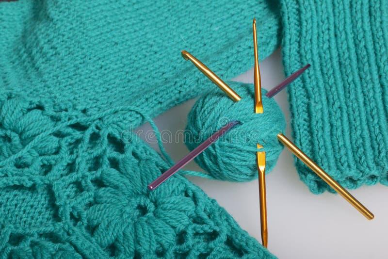Σειρές του νήματος για το σμαραγδένιο χρώμα πλεξίματος και των γάντζων για το πλέξιμο Σε ένα έτοιμο πλεκτό προϊόν στοκ φωτογραφίες