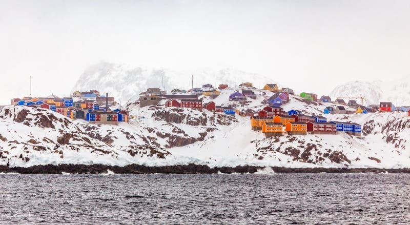Σειρές των ζωηρόχρωμων σπιτιών διαβίωσης Inuit Sisimiut, στους βράχους χιονιού στοκ εικόνες