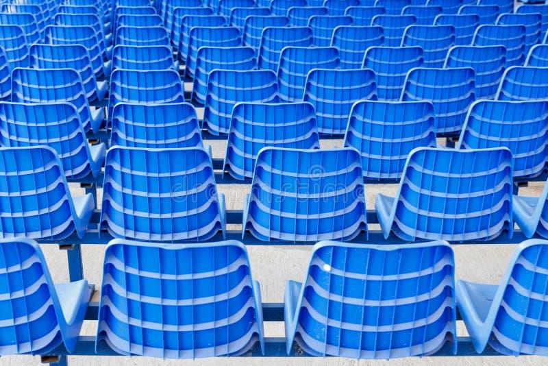 Σειρές των μπλε πλαστικών καρεκλών σε μια βάση μετάλλων υποστηρίξτε την όψη στοκ εικόνες
