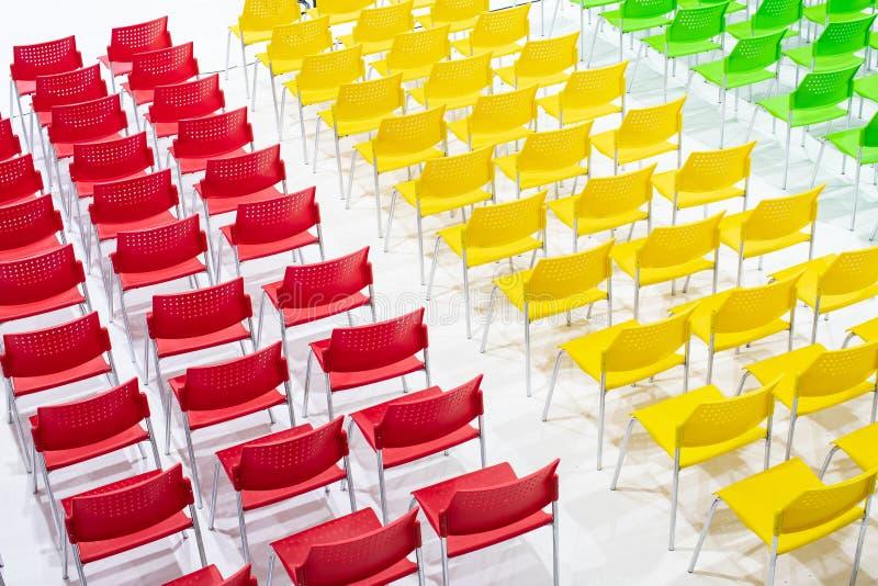 Σειρές των φωτεινών καρεκλών χρώματος που τακτοποιούνται στην αίθουσα συνεδριάσεων έτοιμη στο Si στοκ εικόνα με δικαίωμα ελεύθερης χρήσης