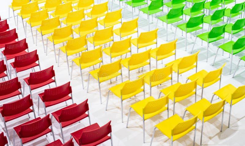 Σειρές των φωτεινών καρεκλών χρώματος που τακτοποιούνται στην αίθουσα συνεδριάσεων έτοιμη στο Si στοκ εικόνες