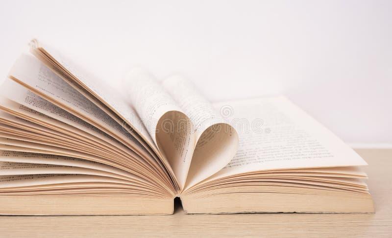 Σελίδα του βιβλίου που κάμπτεται στη μορφή καρδιών στον ξύλινο πίνακα στοκ φωτογραφία με δικαίωμα ελεύθερης χρήσης