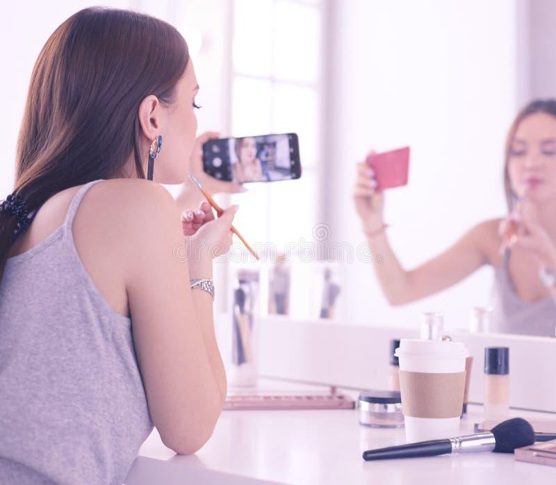 Σεμινάριο μαγνητοσκόπησης ομορφιάς blogger makeup με το smartphone μπροστά από τον καθρέφτη στοκ φωτογραφίες με δικαίωμα ελεύθερης χρήσης