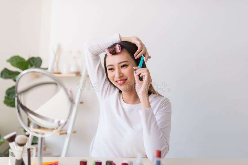 Σεμινάριο Hairstyle Ασιατική γυναίκα που βουρτσίζει την τρίχα της και που χαμογελά ευχάριστα ενώ μαγνητοσκόπηση ένα σεμινάριο για στοκ φωτογραφίες με δικαίωμα ελεύθερης χρήσης