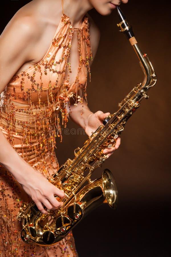Σεξουαλική νέα τοποθέτηση γυναικών με το saxophone στο στούντιο στοκ φωτογραφία