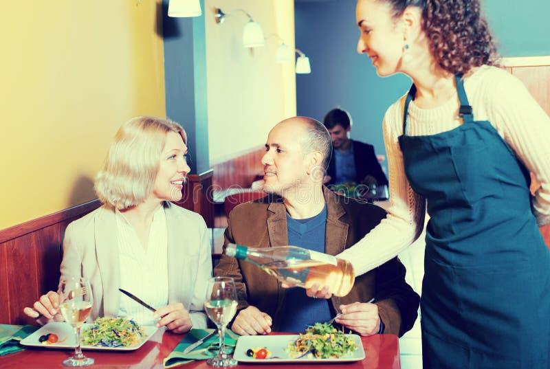 Σερβιτόρα με τους ώριμους φιλοξενουμένους στοκ φωτογραφία