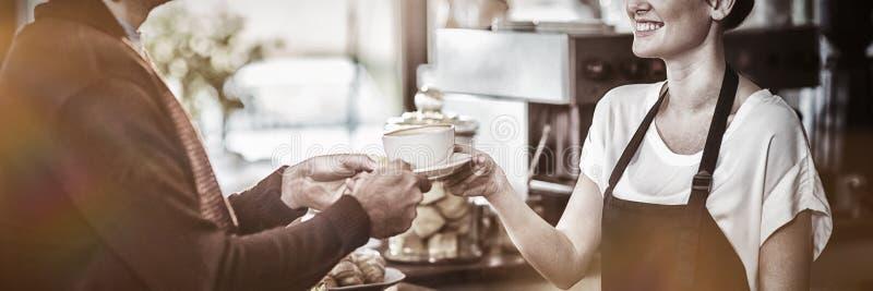 Σερβιτόρα που ένα φλιτζάνι του καφέ στον πελάτη στοκ φωτογραφίες