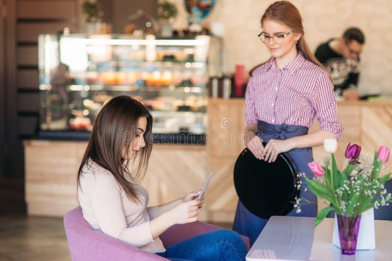 Σερβιτόρα που παίρνει τη διαταγή από τον πελάτη της σε έναν καφέ στοκ εικόνα