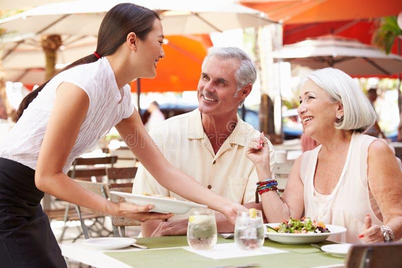 Σερβιτόρα που το ανώτερο μεσημεριανό γεύμα ζεύγους στο υπαίθριο εστιατόριο στοκ φωτογραφίες