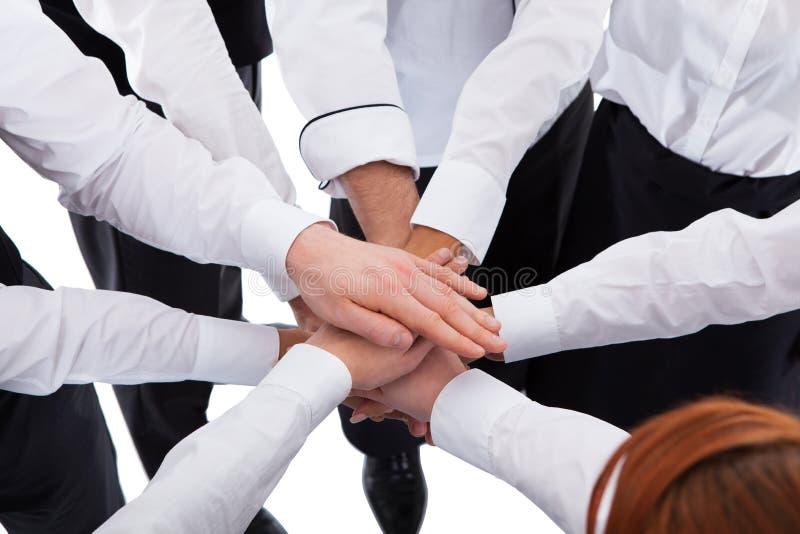 Σερβιτόροι και σερβιτόρες που συσσωρεύουν τα χέρια στοκ εικόνα