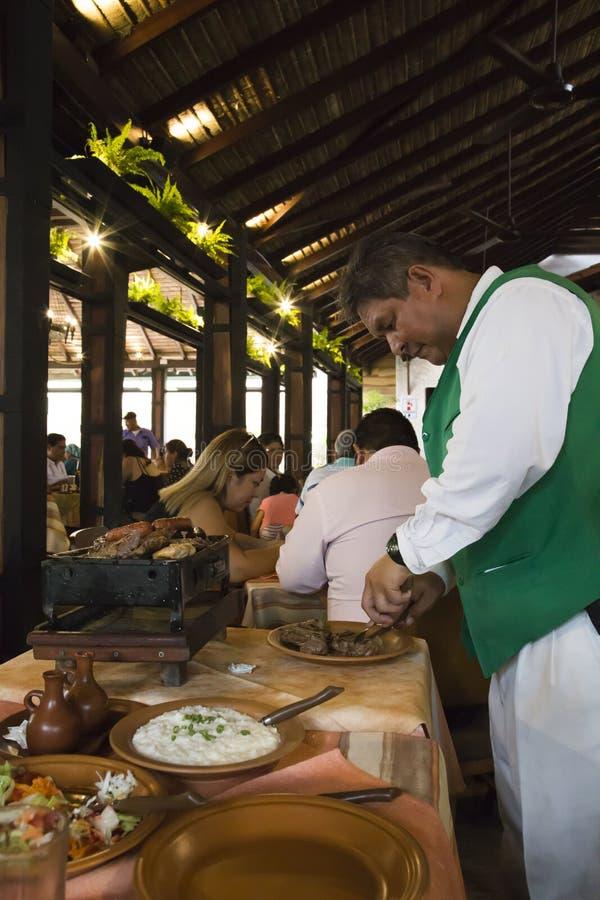 Σερβιτόρος που προετοιμάζει τα τρόφιμα σε ένα εστιατόριο στη Βολιβία στοκ φωτογραφίες