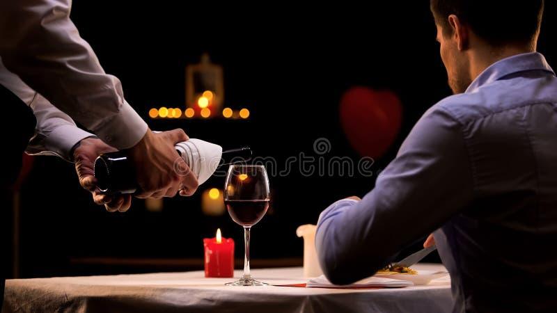 Σερβιτόρος που χύνει στον αρσενικό πελάτη το υψηλής ποιότητας κόκκινο κρασί, νόστιμο γεύμα στο εστιατόριο στοκ εικόνα με δικαίωμα ελεύθερης χρήσης