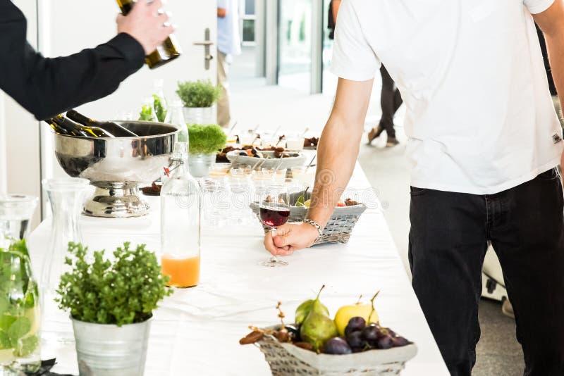 Σερβιτόρος που χύνει το γυαλί κόκκινου κρασιού σε δύο άτομα στον άσπρο πίνακα μπουφέδων στοκ φωτογραφίες