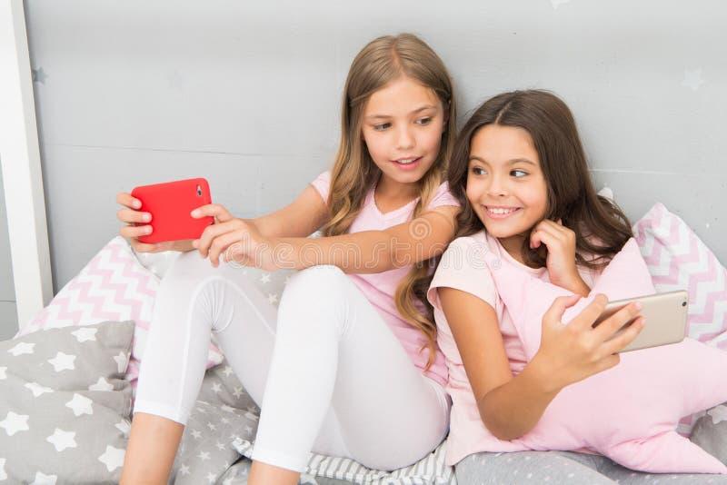 Σερφ Διαδικτύου και γονικός συμβουλευτικός απουσίας Πρόσβαση Διαδικτύου Smartphone Οι αδελφές κοριτσιών φορούν την πυτζάμα πολυάσ στοκ εικόνες με δικαίωμα ελεύθερης χρήσης