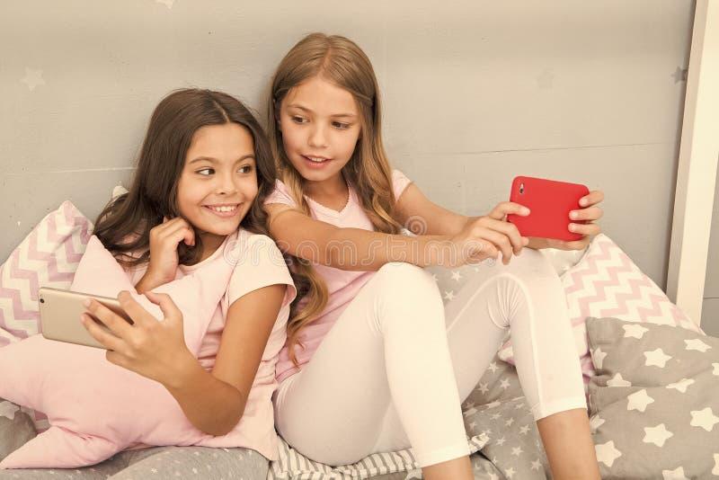 Σερφ Διαδικτύου και γονικός συμβουλευτικός απουσίας Πρόσβαση Διαδικτύου Smartphone Οι αδελφές κοριτσιών φορούν την πυτζάμα πολυάσ στοκ εικόνα με δικαίωμα ελεύθερης χρήσης