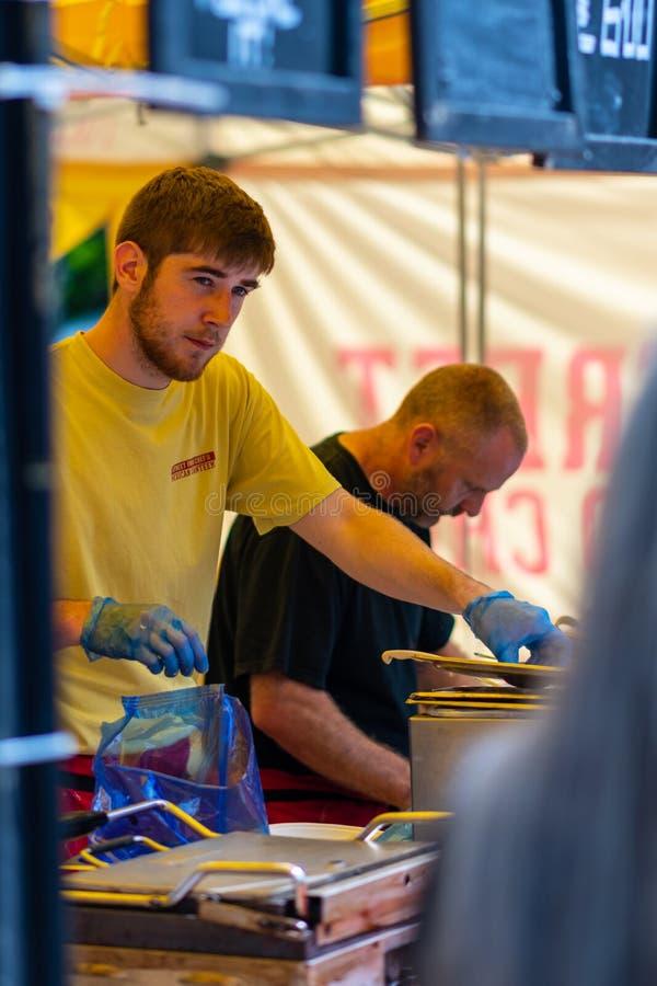 ΣΕΦΙΛΝΤ, UK - 20 ΙΟΥΛΊΟΥ 2019: Τα μέλη του αρχιμάγειρα τροφίμων Steet μαγειρεύουν τα τρόφιμα για τους ανθρώπους κατά τη διάρκεια  στοκ φωτογραφίες
