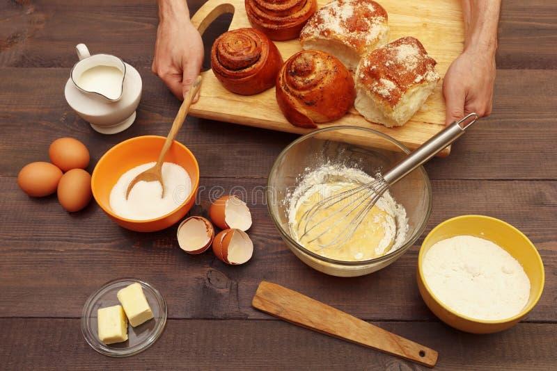Σεφ χεράκια με ψημένα ψωμάκια στο φόντο των συστατικών σε ξύλινο τραπέζι στοκ εικόνες με δικαίωμα ελεύθερης χρήσης